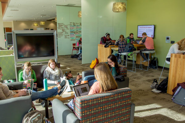 photo of students studying in groups by the windows in the Curran Commons
