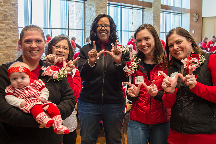 "photo of School of Nursing Dean Linda Scott with School of Nursing alumni dressed in Badger red, making the Wisconsin ""W"" symbol with their hands"