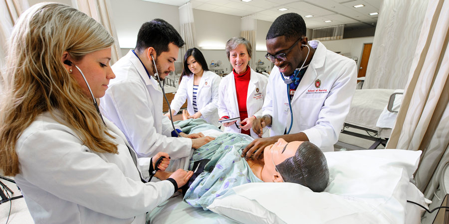 photo of nursing students working with a mannequin in a simulation suite