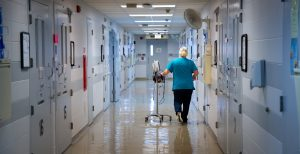 A Nurse walking down a hospital hallway with locks on the doors in the medical wing of the Dodge Correctional Institution.