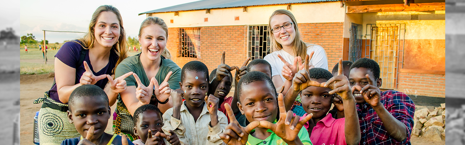 "Student Nurses in Malawi, posing with cute, Malawi children making the ""W"" symbol with their hands."